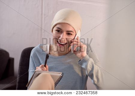 Smiling Young Woman In Kerchief Talking By Smartphone And Taking Notes