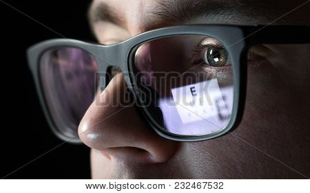 Eye Test And Exam Concept. Close Up Of Man With Glasses At Optician To Test Vision And Sight. Eyesig
