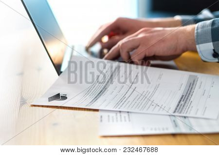 Young Man Writing College Or University Application Form With Laptop. Student Applying To School. Sc