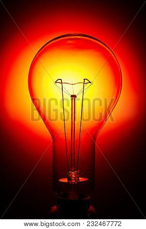 An Old Incandescent Light Bulb Is Photographed In The Dark So That One Of Its Contours Can Be Seen