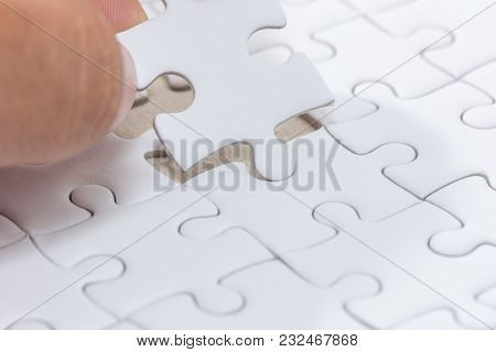 Hand Holding Piece Of White Jigsaw Puzzle
