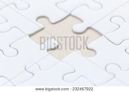 Close Up Of White Jigsaw Puzzle With Missed Piece