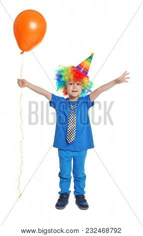 Cute little boy in rainbow wig with balloon on white background. April fool's day celebration