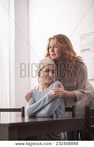 Mature Woman Hugging And Supporting Sick Daughter In Kerchief