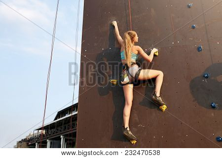Young Caucasian Strong Woman Practicing Climbing On Artificial Rock Wall. Slim Sporty Blonde Trainin