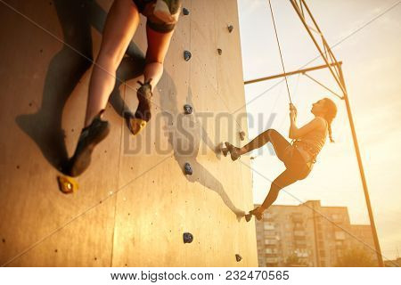 Bottom View Of Two Young Climbers Practice On Artificial Climbing Wall. Active Sporty Women Compete
