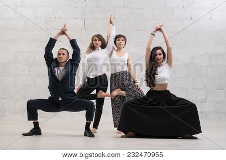 People Wearing Office Clothes Doing Yoga Shot Against White Brick Wall