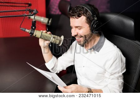 Smiling Young Male Radio Presenter With Headphones Reading A Script And Talking Into A Mic In A Radi