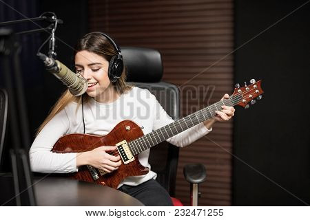 Young Female Singer Playing Guitar And Singing In Microphone At Radio Station