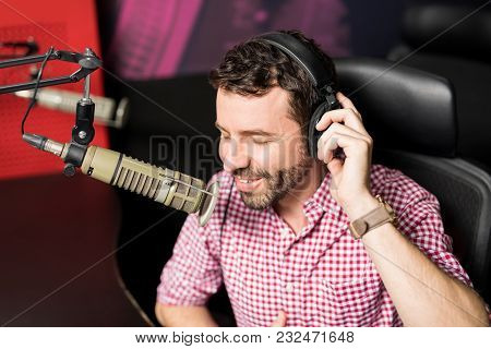 Cheerful Male Radio Presenter With Headphones Talking On Microphone In Radio Station