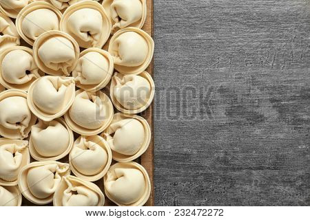 Wooden board with raw dumplings on grey background