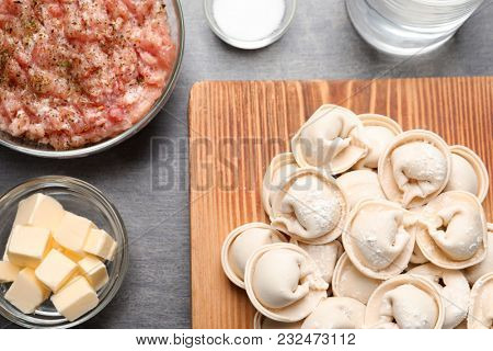 Wooden board with raw dumplings and products on grey background