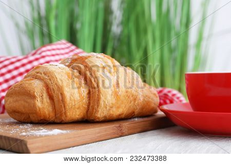 Wooden board with tasty croissant on table