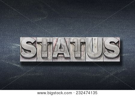 Status Word Made From Metallic Letterpress On Dark Jeans Background