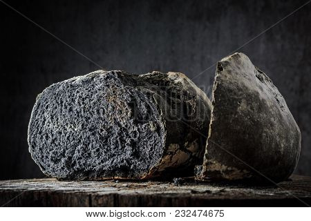 Bread Of Unusual Black Color On A Dark Background On A Wooden Table