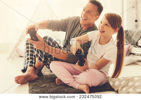 Time For Entertainment. Happy Cheerful Delighted Girl Holding A Game Console And Playing Video Games