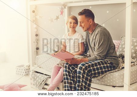 Bedtime Stories. Positive Handsome Nice Man Sitting Together With His Daughter And Smiling While Rea