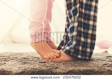 Family Relationships. Close Up Of A Cute Nice Small Girl Standing On The Fathers Feet While Being At