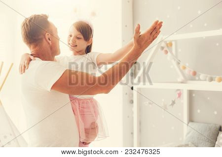 My Princess. Cute Pleasant Happy Girl Smiling And Holding Her Fathers Hand While Dancing With Him