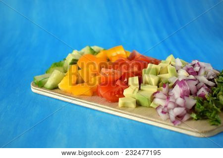 Chopped Vegetables On A Wooden Board. Salad Ingredients On Blue Background