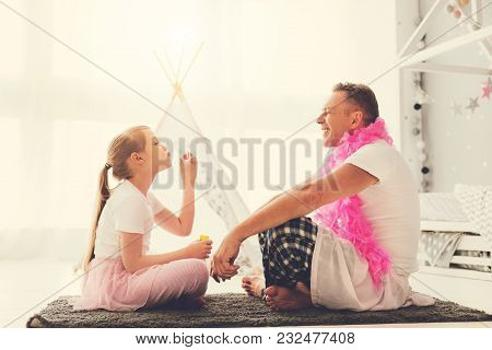 Happy Fatherhood. Cheerful Cute Positive Girl Sitting Opposite Her Father And Smiling While Blowing