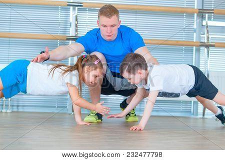Group Of Children Doing Kids Gymnastics In Gym With Teacher. Happy Sporty Children In Gym Bar Exerci
