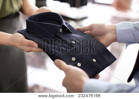 Female shop assistant helping man to choose shirt in store