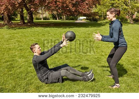 Man throws fitness ball to Personal Trainer at the park
