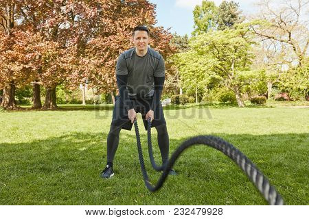 Man moves rope as functional fitness training at the park