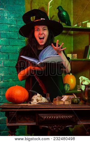 Image of witch with book at table with pumpkin, skull
