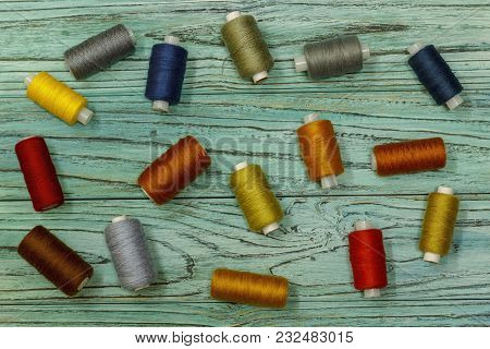 Set Of Multicolored Threads For Sewing And Embroidering On A Wooden Background. Hobbies, Clothes Rep