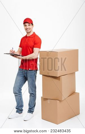 Image of a handsome smiling young delivery man in red cap standing with parcel post boxes isolated over white background. Looking camera.