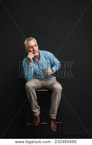 Full length photo of caucasian male pensioner 60s with grey hair and beard sitting on chair and looking aside with brooding view isolated over black background