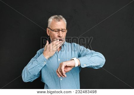 Photo of mature unshaved man 60s with grey hair wearing eyeglasses looking at his wrist watch with confusion isolated over black background