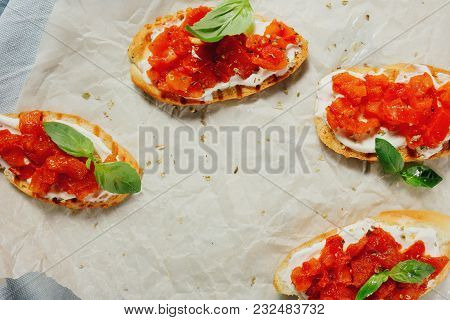 Bruschetta With Soft Cheese, Basil And Cherry Tomatoes On A Paper Background. Easy Vegetarian Italia