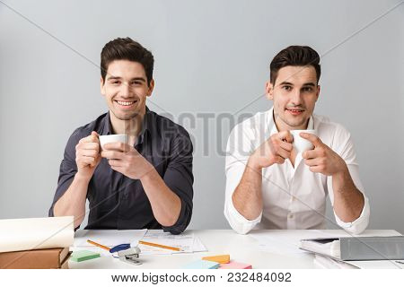 Image of handsome two smiling young business men colleagues sitting isolated over grey wall at the table coworking. Looking camera drinking coffee.