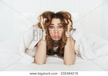 Portrait of an upset young woman lying in bed under the blanket at home and looking at camera