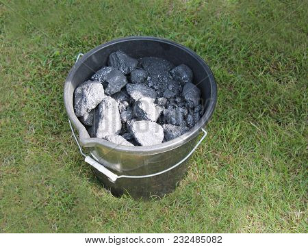 A Plastic Bucket Of Coal In A Grass Field.