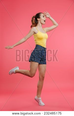 Full length portrait of a happy young girl dressed in summer clothes looking far away while posing isolated over pink background