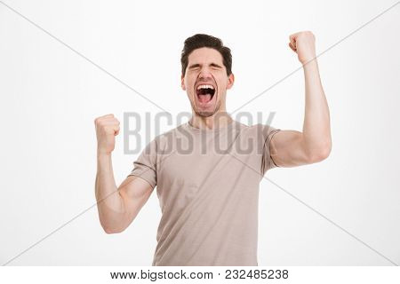 Photo of ecstatic guy 30s in beige t-shirt shouting as celebrating his triumph with clenched fists isolated over white background