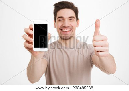 Photo of man in beige t-shirt demonstrating copyspace black screen of smartphone and gesturing thumb up isolated over white wall