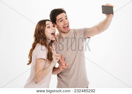 Portrait of two happy people man and woman making selfie on smartphone and smiling broadly with victory gesture isolated over white background
