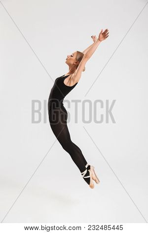 Photo of charming young woman ballerina dancing gracefully over white wall background isolated. Looking aside.