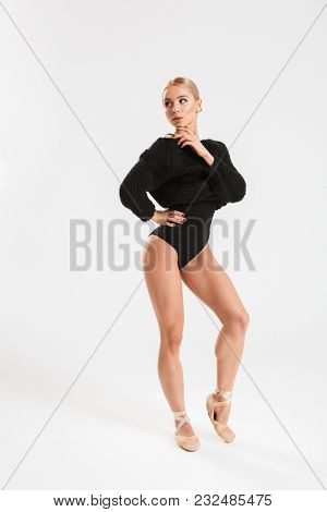 Image of a beautiful young woman ballerina dancing gracefully over white wall background isolated. Looking aside.