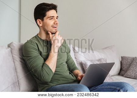 Pensive young man using laptop computer while sitting on a sofa at home