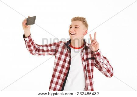 Smiling guy with braces showing peace sign on camera while photographing himself on cell phone isolated over white background