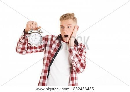 Picture of young hipster man 16y in casual holding and looking at alarm clock counting time for schedule isolated over white background