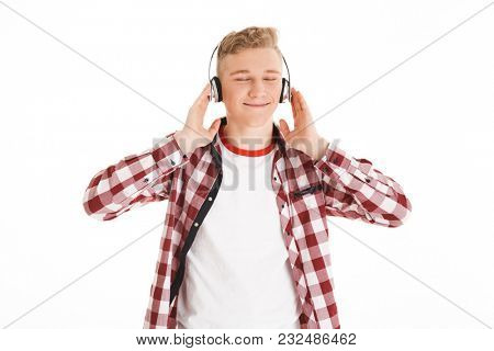 Satisfied teenager in casual t-shirt 17y listening to melody via wireless earphones with closed eyes and feeling pleasure isolated over white background