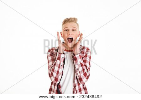 Portrait of an excited schoolboy screaming isolated over white background