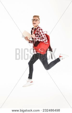 Full length portrait of a cheerful schoolboy in eyeglasses with backpack holding books and jumping isolated over white background